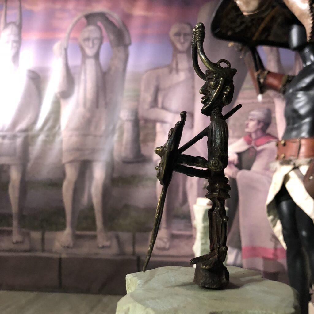 Replik einer Krieger-Bronze vor der Nachbildung der Statuen von Mont'e Prama (temporäre Ausstellung Nuragica, Nuoro)