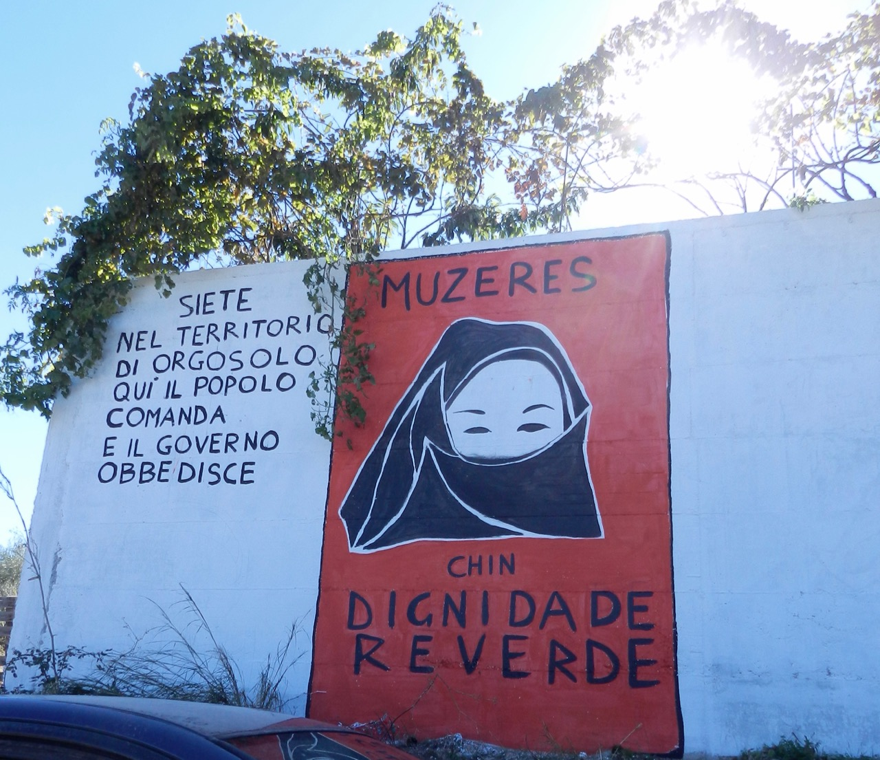 """Satz links im Bild: """"Ihr seid in Orgosolo - wo das Volk regiert und die Regierung gehorcht."""""""
