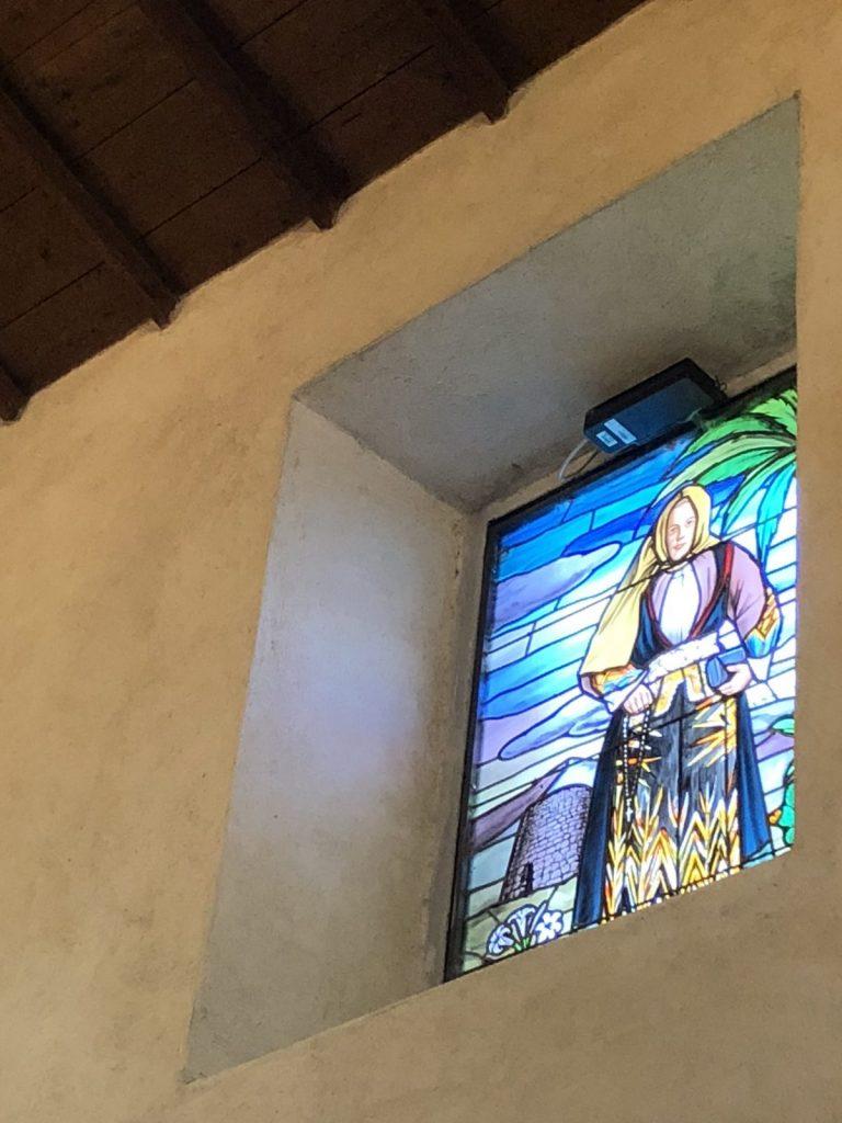 Kirchenfenster mit Sardin in Tracht und Nuraghe